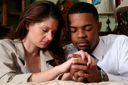 Professional couple kneeling at their bedside in prayer